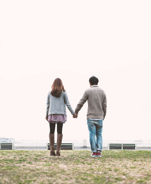 公園で手を繋ぐ男と女