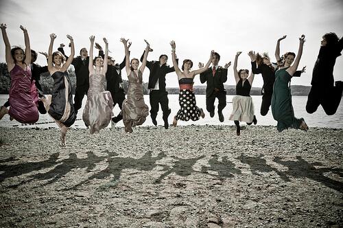 大勢で砂浜で手を上げてジャンプ