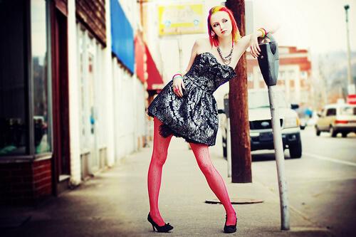 赤髪の派手な白人女性が黒いドレスと赤いタイツを着て立っている
