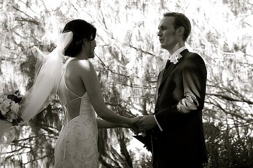 結婚式で手を繋ぎ笑顔で見つめ合う外国人カップル