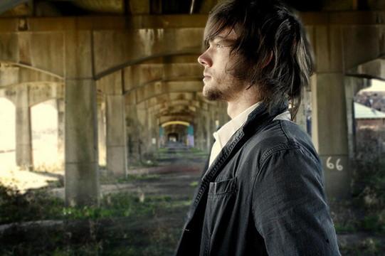陸橋の下で立っている外国人男性の横顔