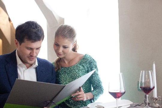 レストランで一緒にメニューを見て料理を選んでいる外国人カップル