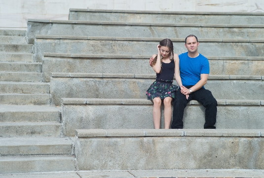 手を繋ぎながら石の階段に座るカップル