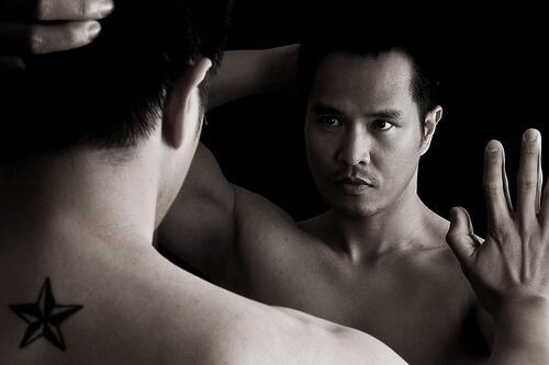 鏡の前で凛々しい表情をしている上半身裸の男
