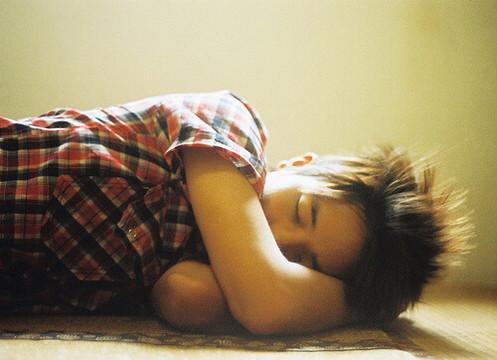 部屋の床で寝てしまっている童顔のアジア人男性