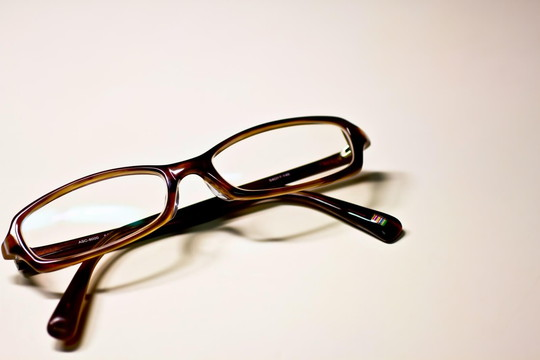 白いテーブルに置かれた茶色のフレームのメガネ