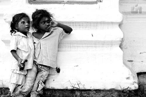 白い壁にもたれかかるインド人の少年と少女