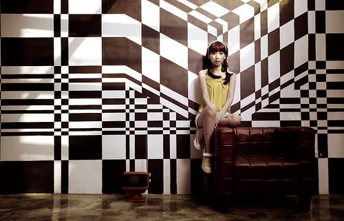 幾何学模様の壁紙の部屋でソファの上に座る少女