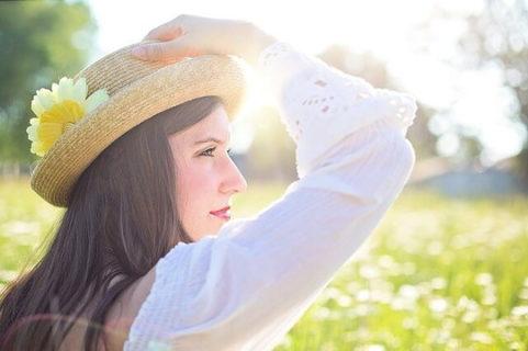 草原で麦わら帽子を押さえるロングヘアの女性