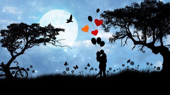 大きな満月の夜にハートの風船を持ってキスをするカップルのシルエット