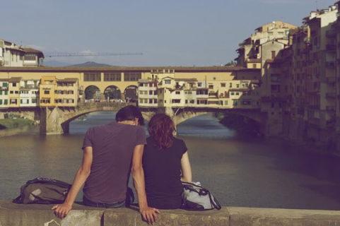 橋の上に腰掛け肩を寄せ合うカップル