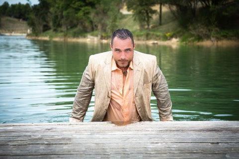 湖から這い上がるスーツを着た外国人男性