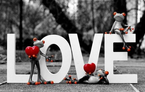LOVEの文字に群がるハートを持ったカエルの人形