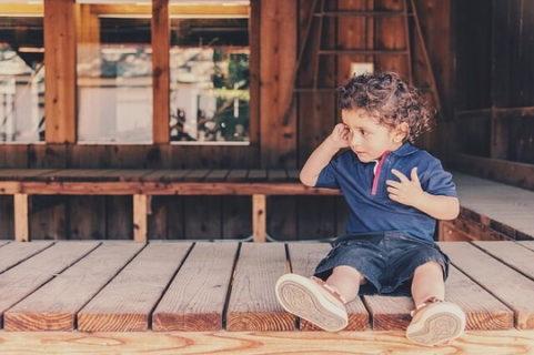 木造の渡り廊下にチョコンと座る外国人の男の子