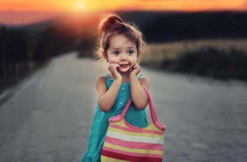 水色のワンピースを着てボーダーのバックを持ちおどけた表情をする外国人の少女