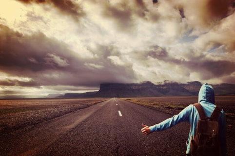 広大な土地でヒッチハイクをするスウェットを着た青年