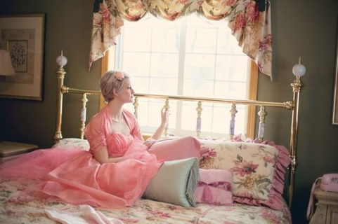 レトロ調の部屋のベッドの上から窓の外を見るピンクの服を着た女性