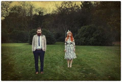 芝生の上で距離を保って立っているヒゲを生やした男性と赤毛の女性