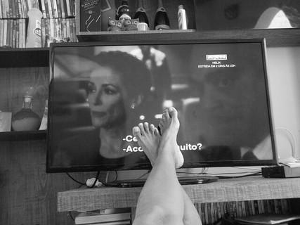 テレビ台に足をかけてひとり自宅で映画を観ている様子