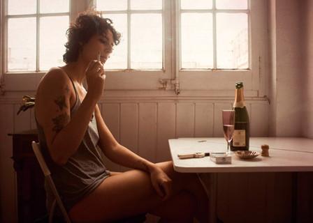 部屋でひとりシャンパンを飲みながらタバコを吸う女性