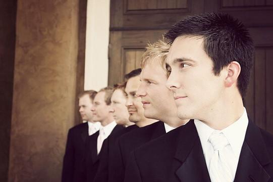 一斉に同じ方向を向くスーツを着た6人の男性