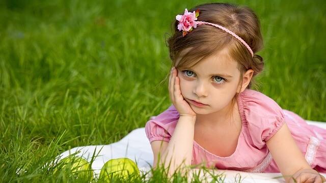 草原で頬杖をついているピンクの服を着た少女