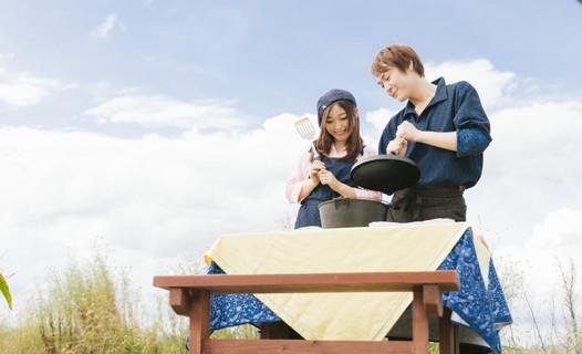 晴れた冬の屋外でダッチオーブンを使い鍋料理を作る幸せそうなカップル