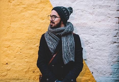 ダッフルコートにマフラーを着用した20代男性