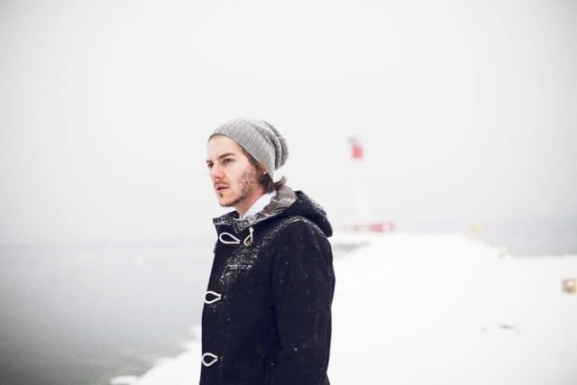 冬らしい色合いのニットキャップとダッフルコートを着た青年