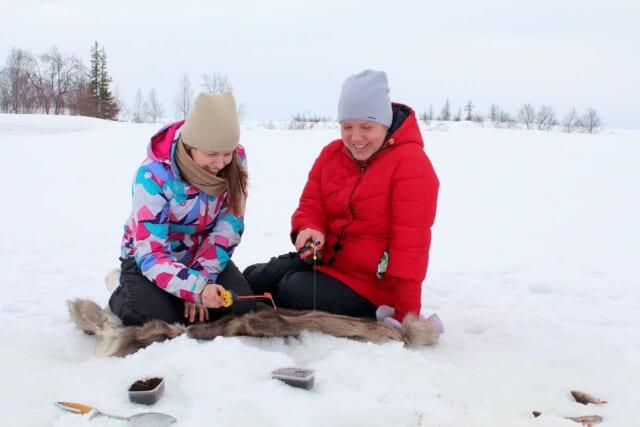 氷上でわかさぎ釣りをするカップル