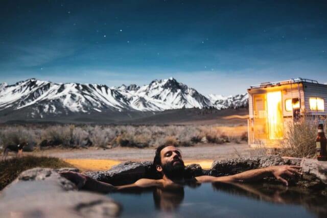 貸切露天風呂の湯船に浸かる男性