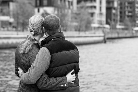 寒い冬のデートで腰に手をまわし寄り添い合い愛情を再確認するカップル