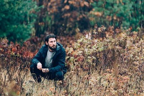 紅葉した良い雰囲気の山中で渋い表情を浮かべるモテそうな中年男性