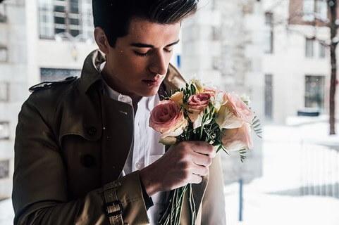女性に愛の告白をするためにバラを手に持つトレンドに敏感そうな男性