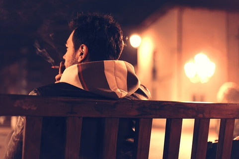 バレンタインの日の夜に女友達を呼び出しベンチで座って待つ男性
