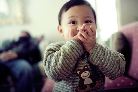 手で口を押さえ可愛らしく笑うショートカットの女の子