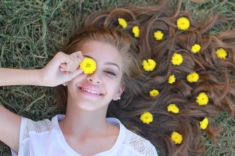 新生活前の休日をたんぽぽの花摘みをして楽しげに過ごす女性