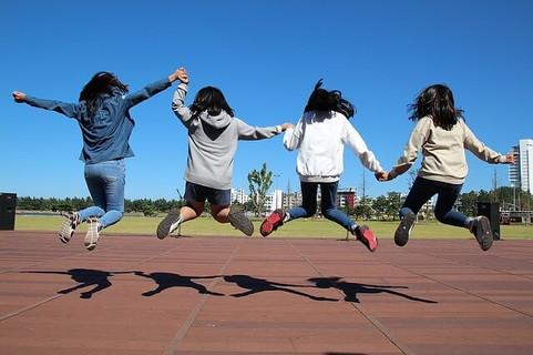 春からの新生活に期待が高まってジャンプする女の子グループ