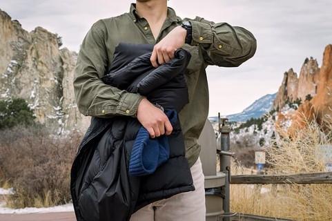 ダウンジャケットを脱ぎアクティブに行動する準備を整えた男性