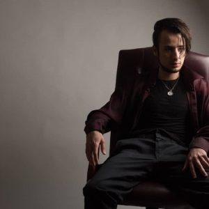 シンプルな部屋で一人掛けソファに腰掛けるモテそうな社会人男性
