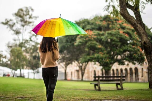 雨続きでスッキリしない気分をカラフルな色使いの傘をもち散歩してリラックス効果を狙う女性
