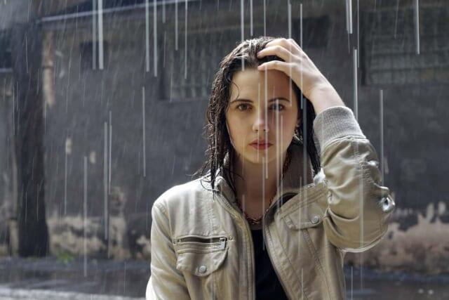 映画のワンシーンのような雨が降りしきるなか立ちつくしジッと見つめる女性