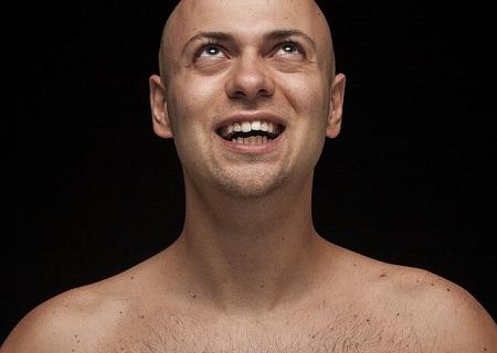 少し上向きなテンションで笑顔を浮かべる男