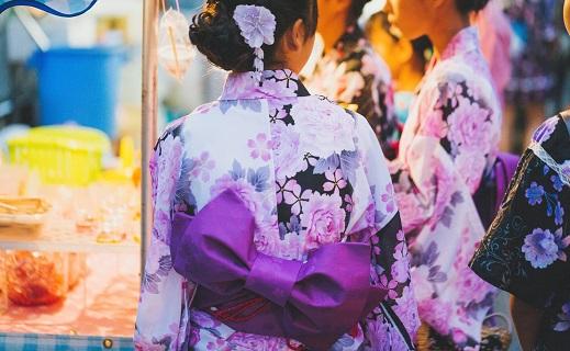 花火大会の出店に並ぶ浴衣を着た女性のうしろ姿