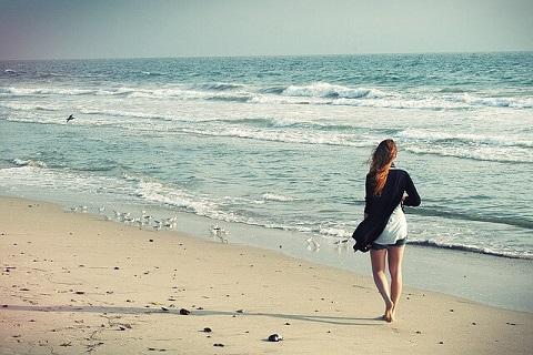 夏の終わりにもの悲しさを感じつつ砂浜を散歩する女性