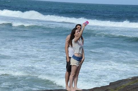 夏に出会った男女が夏の終わりに付き合いはじめ記念で海をバックに記念撮影