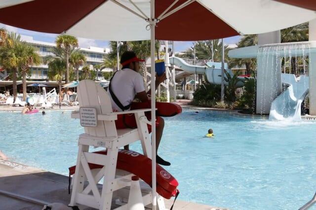 のんびりとしたプールで監視員のバイトをする青年