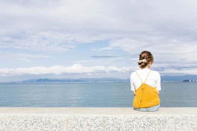 人見知りの性格が関係して彼ができないと海を眺めながらたそがれる女性