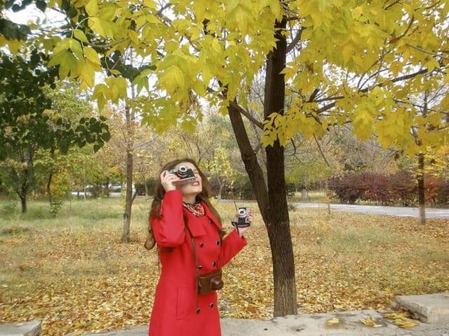 紅葉しかけている葉を写真撮影する女性