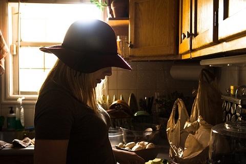 キッチンに立ち大切な人のために料理をする女性の画像です。
